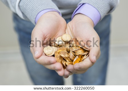 Handful of coins in palm hands - stock photo