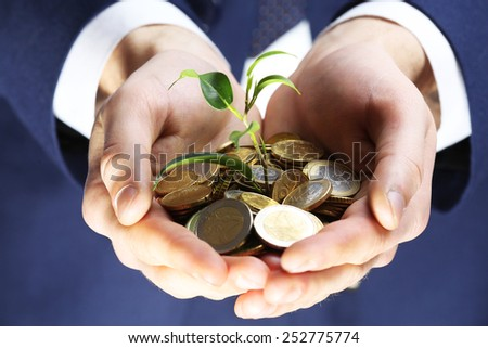 Handful of coins with growing sprout, closeup view - stock photo