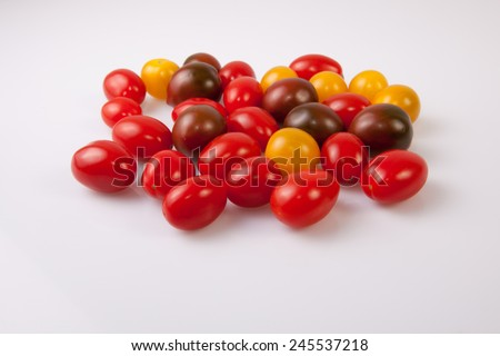 Handful of colorful cherry tomatoes. Isolated over white background