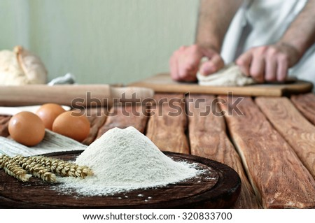 Handful of flour on a rustic kitchen. Against the background of men's hands knead the dough. Copy space. Free space for text - stock photo