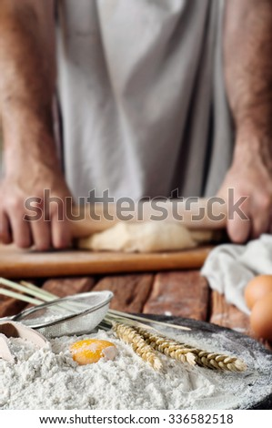 handful of flour with egg on a rustic kitchen. Against the background of men's hands knead the dough. Ingredients for cooking flour products or dough. Copy space - stock photo