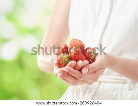 Handful of fresh ripe juicy strawberries in hands of young woman in white dress on nature background. Healthy eco sweet food rich in vitamins. Popular product of organic farming. - stock photo