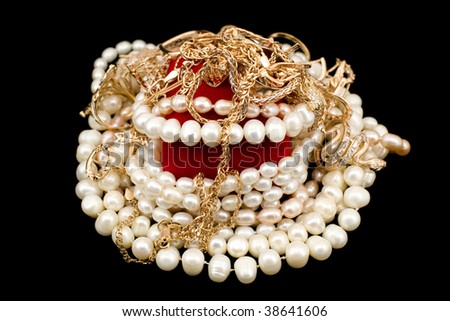 Handful of gold and pearls isolated on a black background
