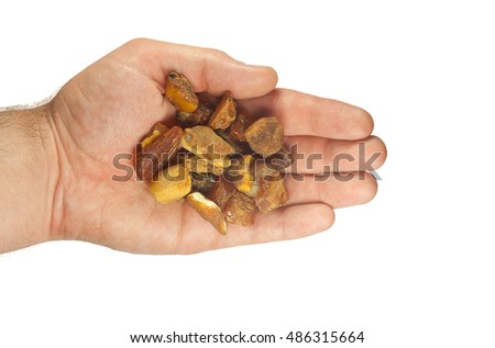 handful of large pieces of amber in palms on white background