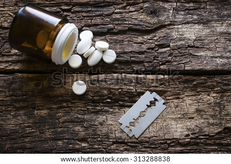 handful of pills and blade for suicide on a wooden background - stock photo