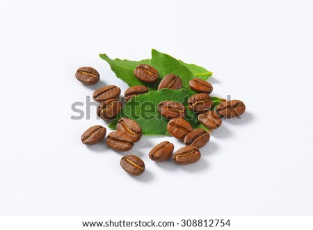Handful of roasted coffee beans on white background