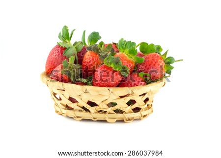 Handful of strawberries in a wicker basket on a white background - stock photo