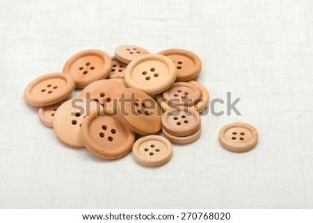 Handful of wooden buttons of various sizes on fabric - stock photo