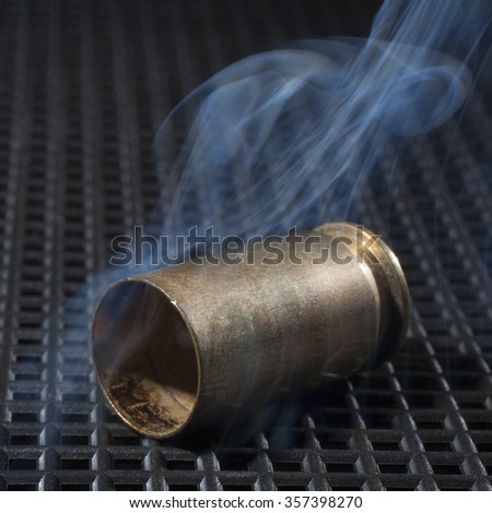 Handgun casing that has been shot and is smoking on a grate - stock photo