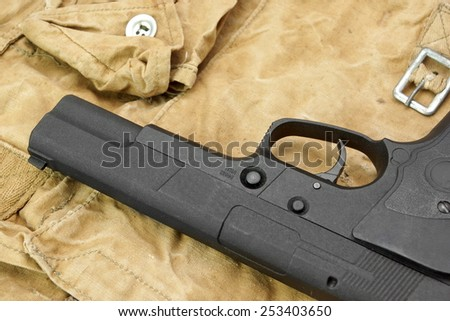 Handgun Lying Over a  Camouflage  Handbag. Background with space for text or image. - stock photo