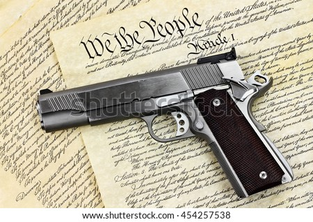 "Handgun lying over a copy of the United States constitution with the words ""We the People"" visible."