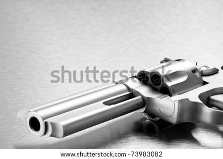handgun on steel background - modern revolver closeup with copyspace. Focus on cylinder. - stock photo