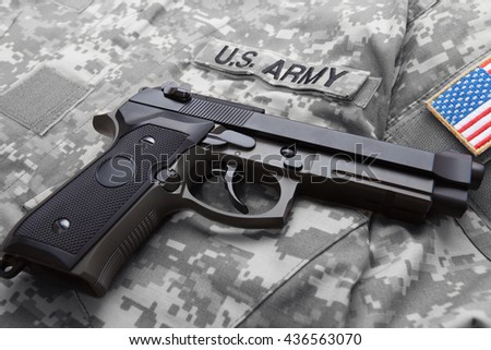Handgun over American soldier's uniform with USA flag shoulder patch on it - stock photo
