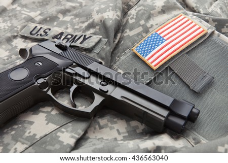 Handgun over USA solder's uniform with USA flag shoulder patch on it - stock photo