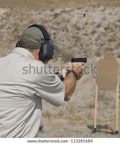Handgun shooter who is target practicing at the range - stock photo