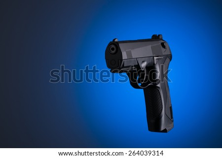 Handgun silouette with blue and black background - stock photo