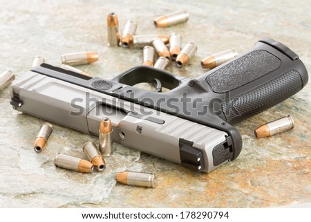 Handgun surrounded with scattered bullets littering the top of an old grungy wooden surface depicting crime, terrorism and violence or protection of personal assets - stock photo