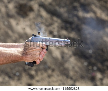 Handgun that has delivered a singe shot with brass in the air - stock photo