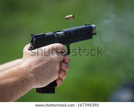 Handgun with brass flying and smoke coming from its barrel