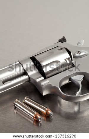 Handgun with bullets - modern revolver on brushed metal with two bullets - stock photo