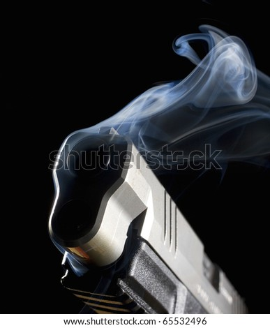Handgun with its muzzle in the dark with smoke coming out - stock photo