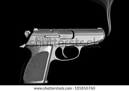 Handgun with smoke emerging from it - stock photo