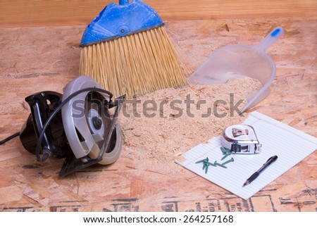 Handheld circular saw with sawdust, brush and pan lying on the floor with a tape measure, pen and nails on a page of paper in a concept of the mess and aftermath of carpentry - stock photo