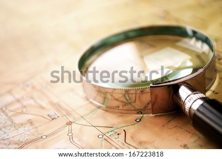 Handheld magnifying glass lying on a map conceptual of search, discovery , planning and exploration - stock photo