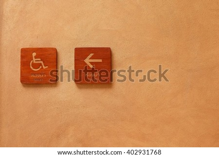 Handicap and toilet wooden signs with cement background - stock photo