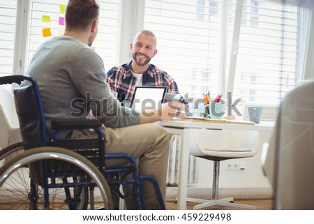 Handicap businessman discussing with colleague in creative office