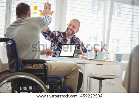 Handicap businessman giving high-five to colleague in creative office