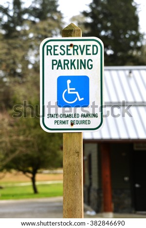 Handicap parking reserved space sign on a wooden post - stock photo