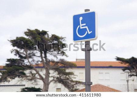 Handicap parking sign on a street in front of a building and trees. - stock photo