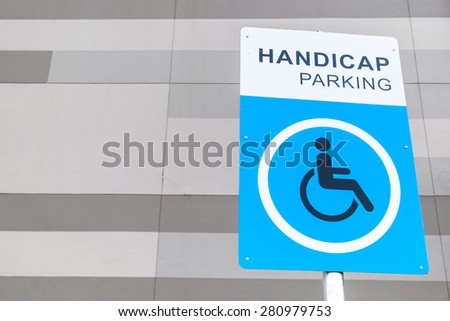 Handicap parking sign post on gray building