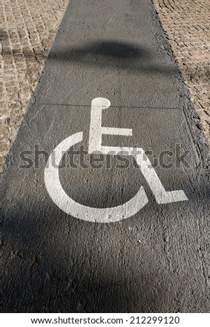 Handicap Sign on Paving - Barcelona Spain / White markings representing a wheelchair, in a route reserved for handicapped in Barcelona, Spain - stock photo