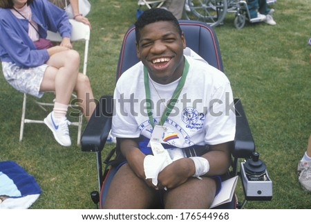 Handicapped African American Athlete cheering at finish line, Special Olympics, UCLA, CA - stock photo