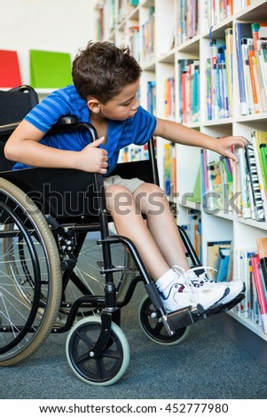 Handicapped boy searching books at library in school