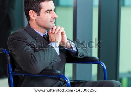 handicapped businessman sitting in a wheelchair looking outside the window - stock photo
