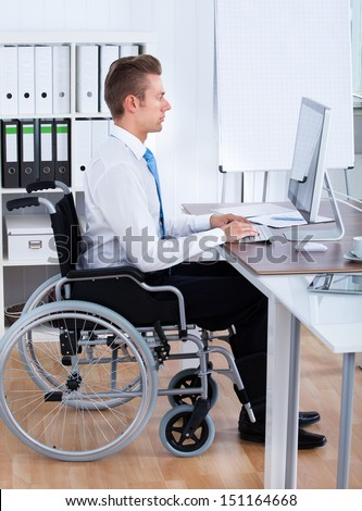 Handicapped Businessman Sitting On Wheelchair And Using Computer In Office - stock photo
