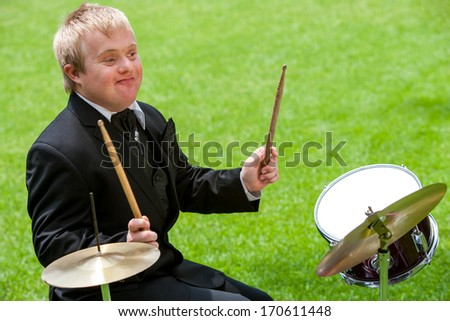 Handicapped drummer boy playing drums outdoors. - stock photo
