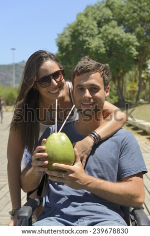 handicapped man in wheelchair and girlfriend drinking coconut water - stock photo