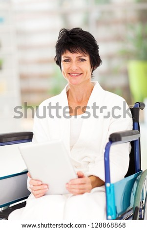 handicapped middle aged woman using tablet computer at home