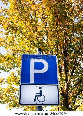 handicapped parking sign and autumn colored tree - stock photo