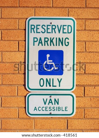 Handicapped parking sign on brick wall