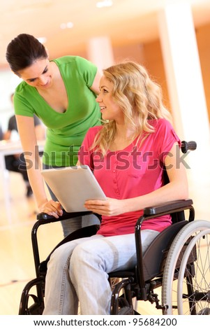 Handicapped person at work with electronic tablet - stock photo