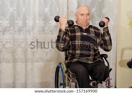 Handicapped senior man with a lower leg amputation working out sitting in his wheelchair using a pair of dumbbells - stock photo