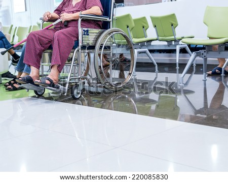 Handicapped senior patient woman on wheelchair in hospital - stock photo