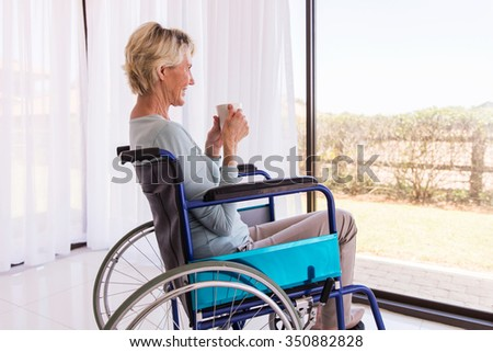 handicapped senior woman drinking coffee at home - stock photo
