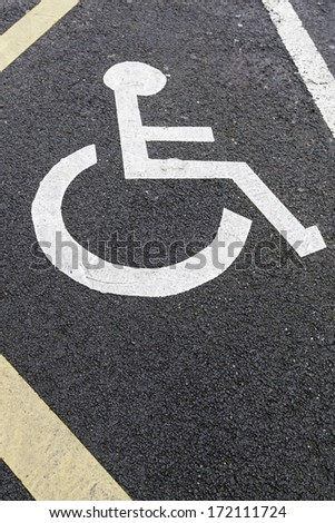 Handicapped sign on asphalt, detail from a diminished signal for people to park, help - stock photo