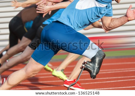 Handicapped sprinter starts short track race with unhindered athletes - stock photo